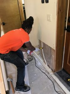 A Technician Repairing Flood Damage at a Residential Property